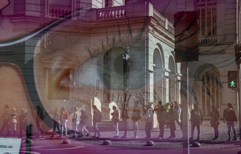 En esta foto de archivo del 17 de agosto de 2020, las personas se reflejan en el escaparate de una tienda de anteojos mientras esperan frente a la oficina de administración de pensiones, AFP, para solicitar un retiro anticipado de un porcentaje de sus pensiones del gobierno el primer día de la levantamiento parcial de las restricciones de cuarentena destinadas a frenar el nuevo coronavirus en el centro de Santiago, Chile. Los legisladores de Chile aprobaron el jueves 15 de abril de 2021 un tercer retiro anticipado de un porcentaje de la pensión de las personas. (AP Foto/Esteban Felix, Archivo)