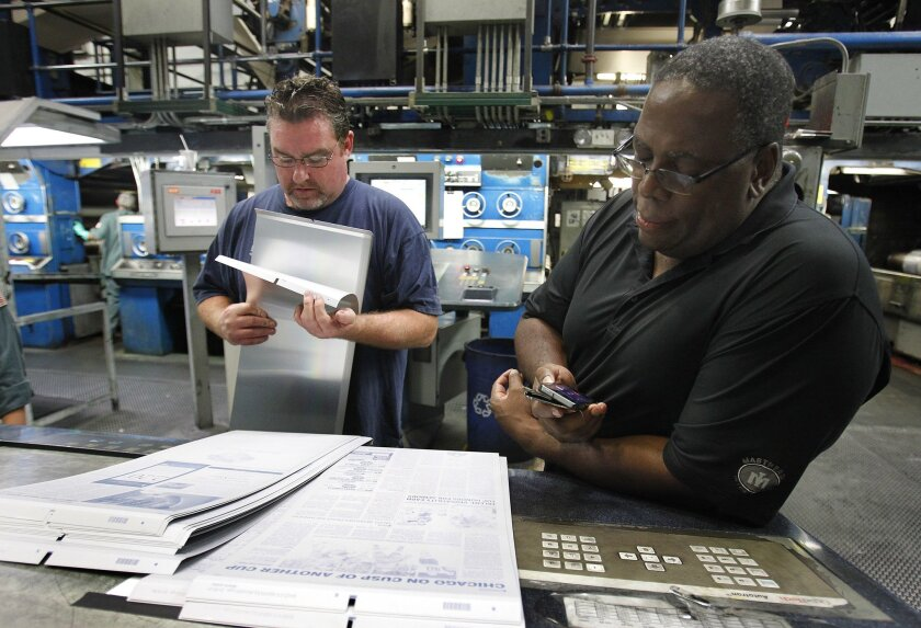 June 13, 2015 - San Diego, CA, U.S. - The final scheduled press run of the San Diego Union-Tribune goes through the presses Saturday night, ending an era. David Allen (L) goes through plates as Pressroom Manager Rob Witherspoon (R) keeps an eye on the time.  San Diego Union-Tribune photo by Howard