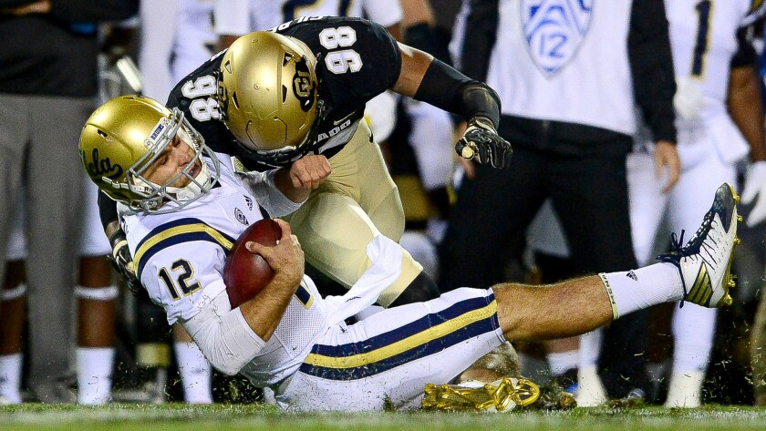 UCLA quarterback Mike Fafaul is brought down by Colorado linebacker Jimmie Gilbert during a play in the first quarter that resulted in a targeting penalty and ejection.