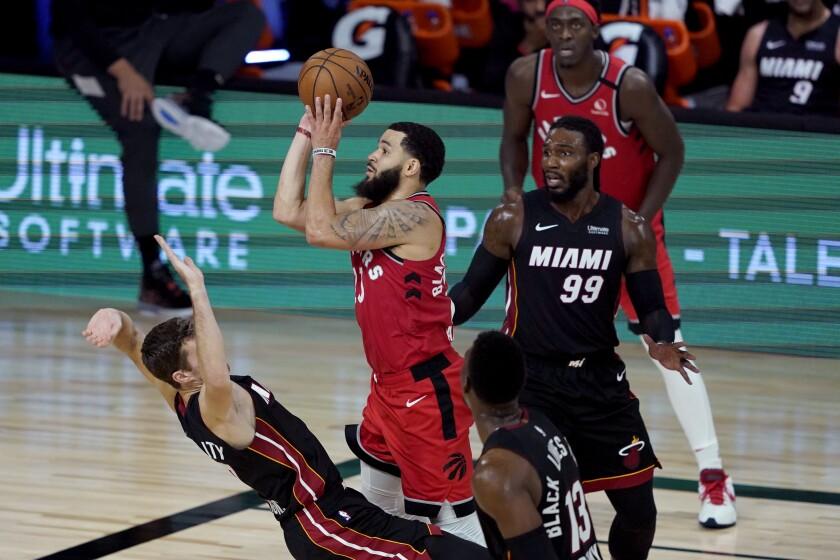 Toronto Raptors' Fred VanVleet shoots as Miami Heat's Goran Dragic tries to draw the offensive foul.