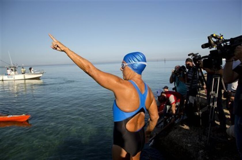 U.S. swimmer Diana Nyad, 64, points towards Florida before her swim to Florida from Havana, Cuba, Saturday, Aug. 31, 2013. Endurance athlete Nyad launched another bid Saturday to set an open-water record by swimming from Havana to the Florida Keys without a protective shark cage. (AP Photo/Ramon Es