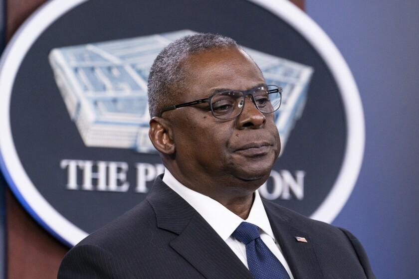 Secretary of Defense Lloyd J. Austin III in front of a Pentagon insignia