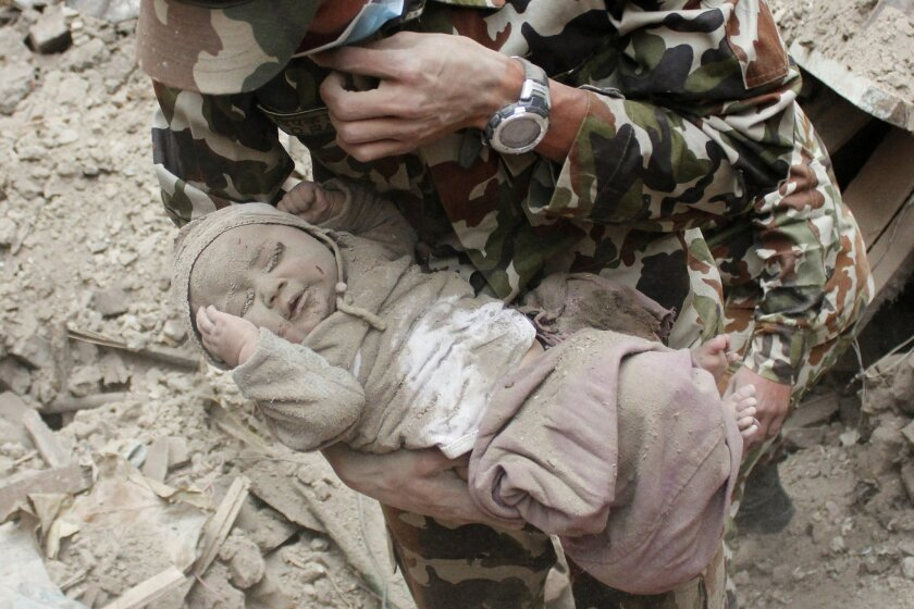 """In this Sunday, April 26, 2015, photo taken by Amul Thapa and provided by KathmanduToday.com, four-month-old baby boy Sonit Awal is held up by Nepalese Army soldiers after being rescued from the rubble of his house in Bhaktapur, Nepal, after Saturday's 7.8-magnitude earthquake shook the densely populated Kathmandu valley. Thapa says that when he saw the baby alive after 20 hours of rescue efforts """"… all my sorrow went. Everyone was clapping. It gave me energy and made me smile in spite of lots of pain hidden inside me."""" (Amul Thapa/KathmanduToday.com via AP)"""