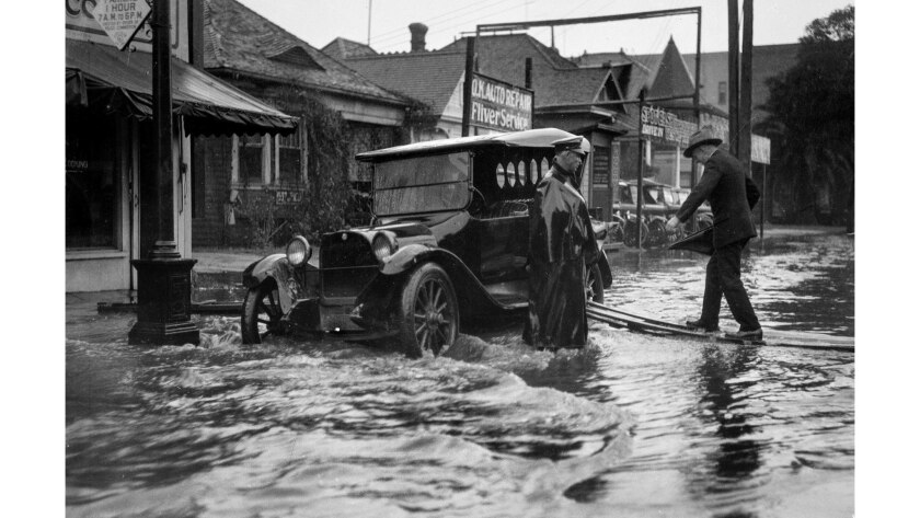 1926: Man is helped to vehicle on Pico Blvd. during flooding. Exact date unknown. A major storms hit