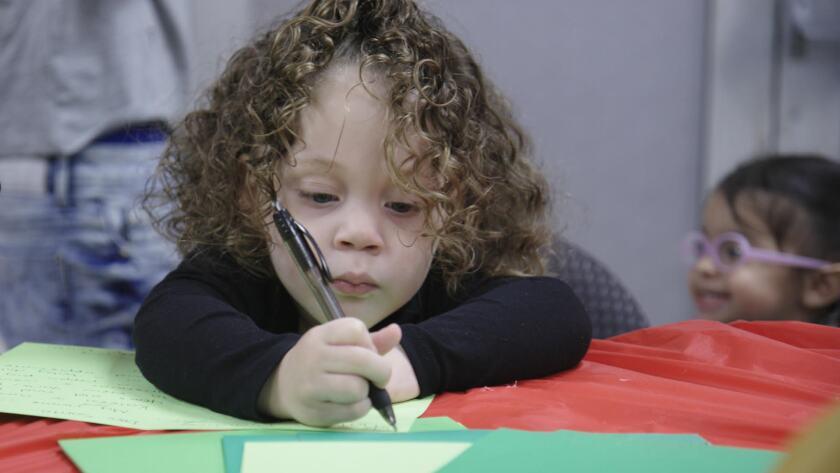 "Putting pen to paper in ""Dear Santa."""