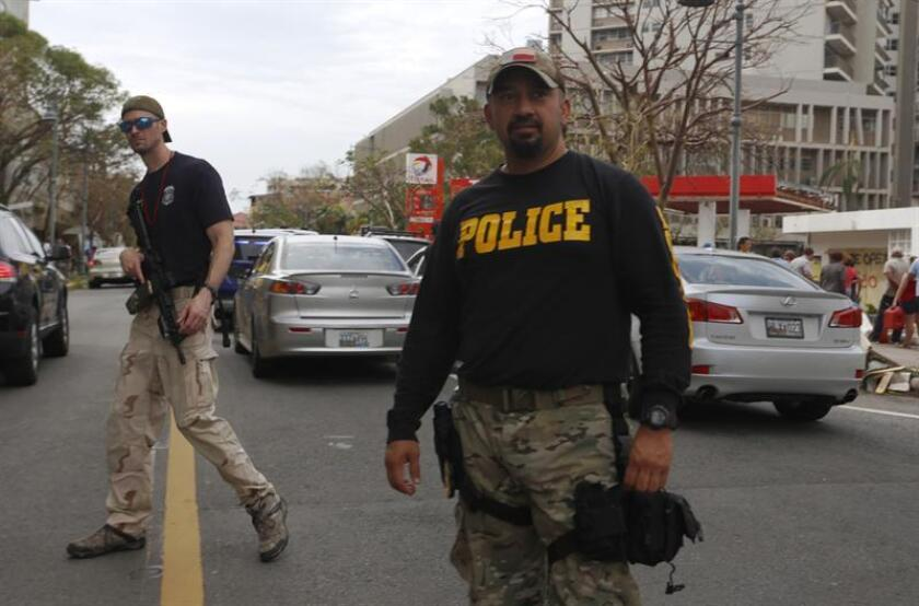 Dos agentes de policía mantienen vigilancia junto una gasolinera en San Juan, Puerto Rico. EFE/Archivo