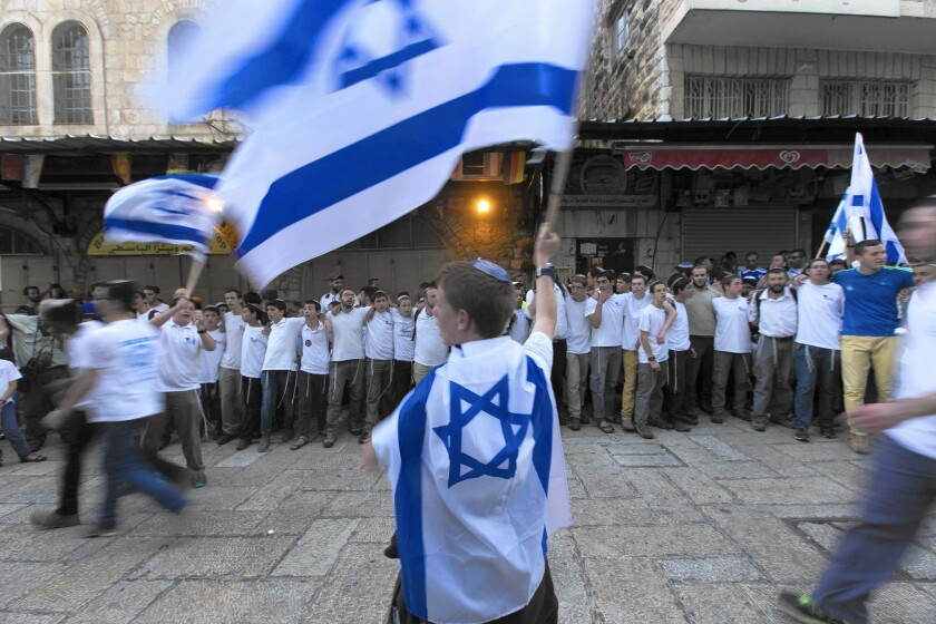 Israelis bearing the national flag stop in the Muslim Quarter while marching through Jerusalem's Old City to mark Jerusalem Day.