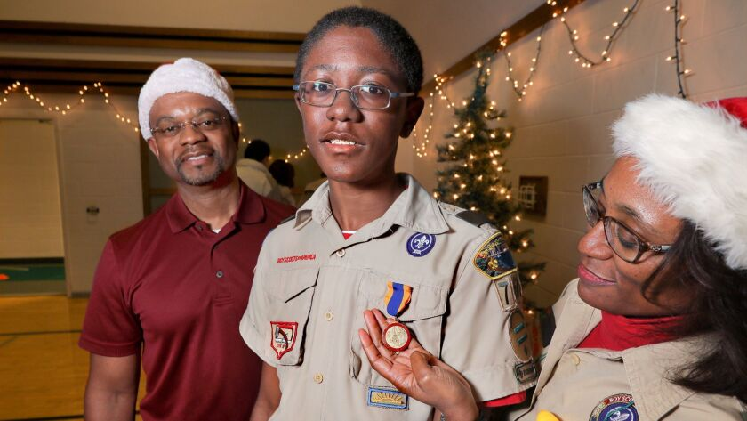 Boy Scout Myles Harris stands with his parents Marc and Karmen Harris. Karmen is holding the Medal of Merit he was awarded for saving her life.
