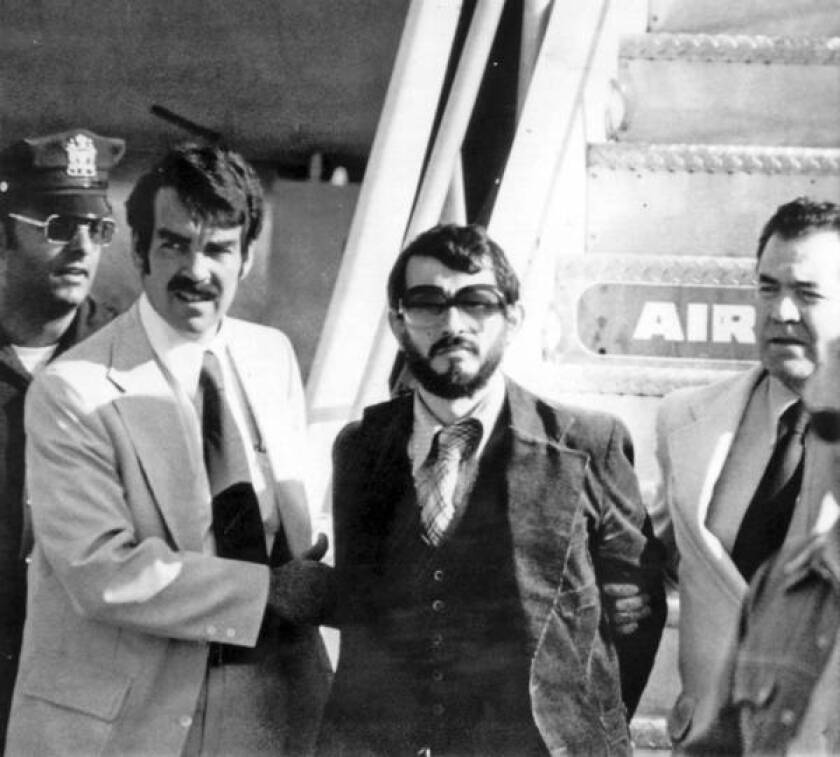 1976 photo shows Zvonko Busic, with beard, being led from plane in custody of police at New York's Kennedy Airport after he and four companions returned from Paris to face charges of air piracy and murder.