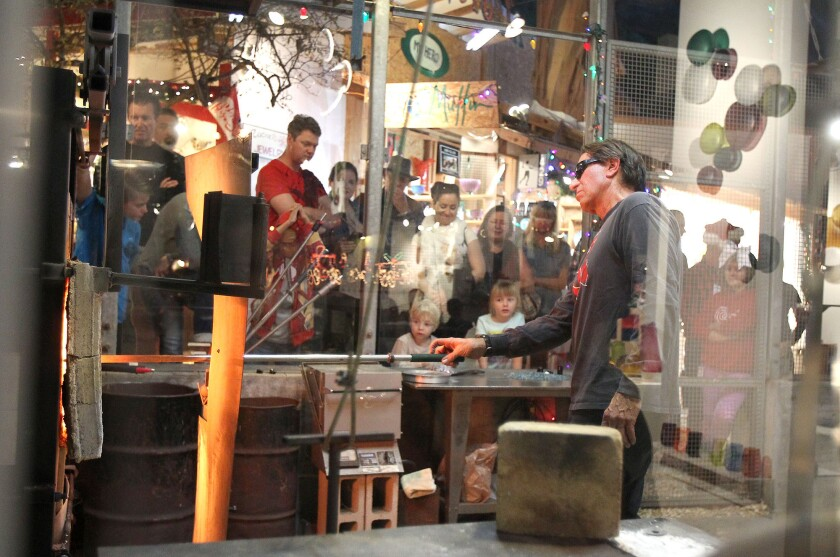 A glass-blower demonstrates the craft at the Sawdust Art Festival's 25th Annual Winter Fantasy in December, one of Laguna Beach's many arts events. The city is seeking more cohesion among its many arts elements.