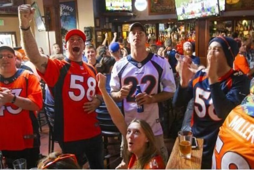 Guava Beach Bar and Grill in Mission Beach plays host to scores of Denver Broncos fans every week as it serves as a hotspot for the NFL team here in San Diego. (Left to right) Jeremy Gates, Mike Hickman, and Edgar Arechiga cheer after the Broncos get a first down while watching the game at Guava Be