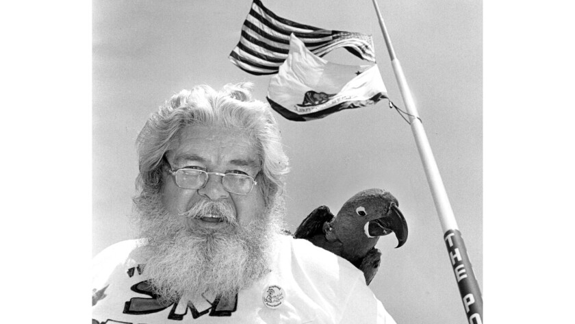 1989 photo of Thomas 'Ski' Demski with his parrot'Peppy' in front of his flagpole in Long Beach.