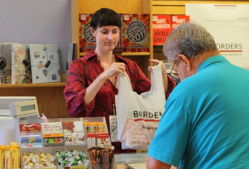 A Borders employee helps a customer at the Mission Valley store prior to Friday's bankruptcy. The book chain will close all its 399 stores nationwide, which employed 10,700.
