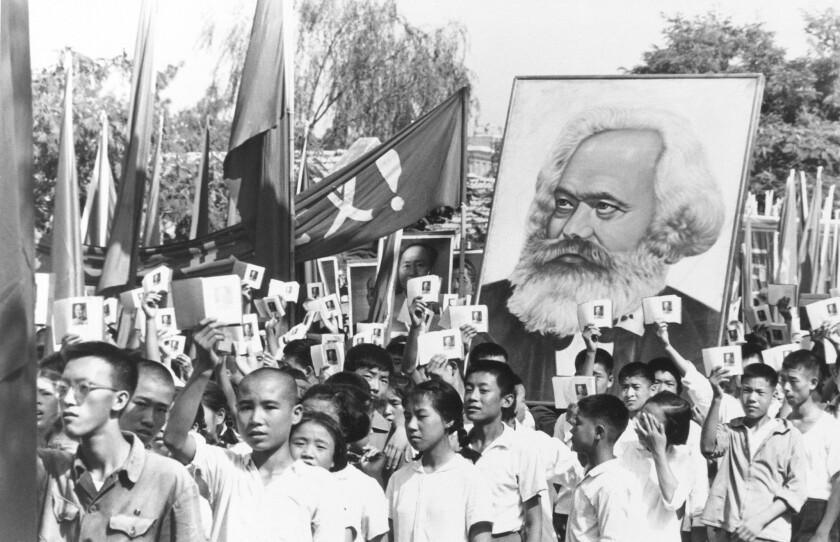 Youths at a rally during the height of the Red Guard upheaval wave copies of Mao's Little Red Book and carry a poster of Karl Marx.