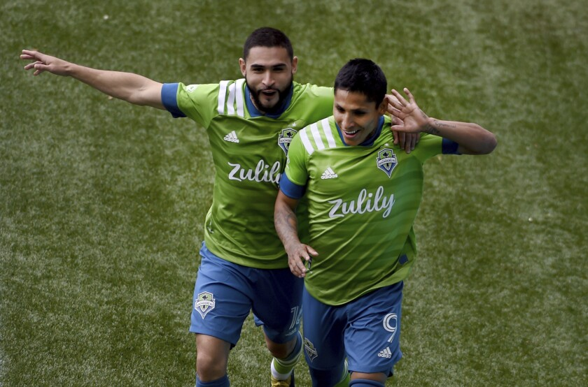 Seattle Sounders forward Raul Ruidiaz, right, celebrates with midfielder Alex Roldan, left, after scoring during second half of an MLS soccer match against the Portland Timbers in Portland, Ore., Sunday, May 9, 2021. (AP Photo/Steve Dykes)