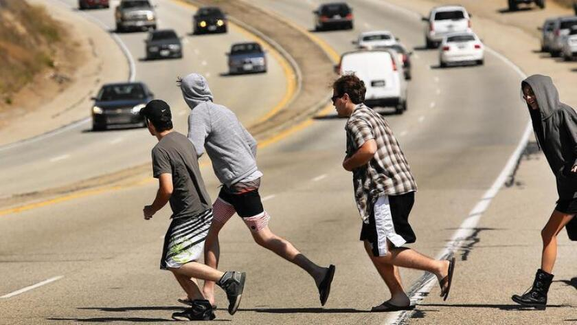 Pedestrians run to cross Pacific Coast Highway in Malibu as vehicles speed past in April. As of June, four people had died in 117 accidents in 2015 along the Malibu portion of PCH, according to the Los Angeles County Sheriff's Department.