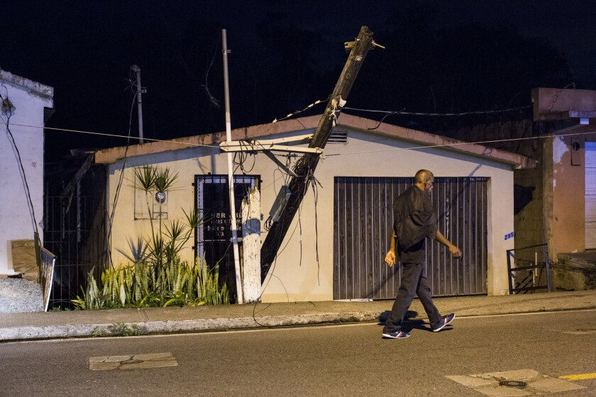 A broken utility pole hangs in front of a structure in Cayey, Puerto Rico, on March 1.