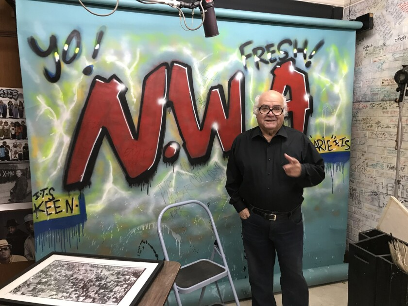 Photographer George Rodriguez in his downtown Los Angeles studio in April 2018. Behind him is a backdrop he employed for an early shoot with N.W.A.