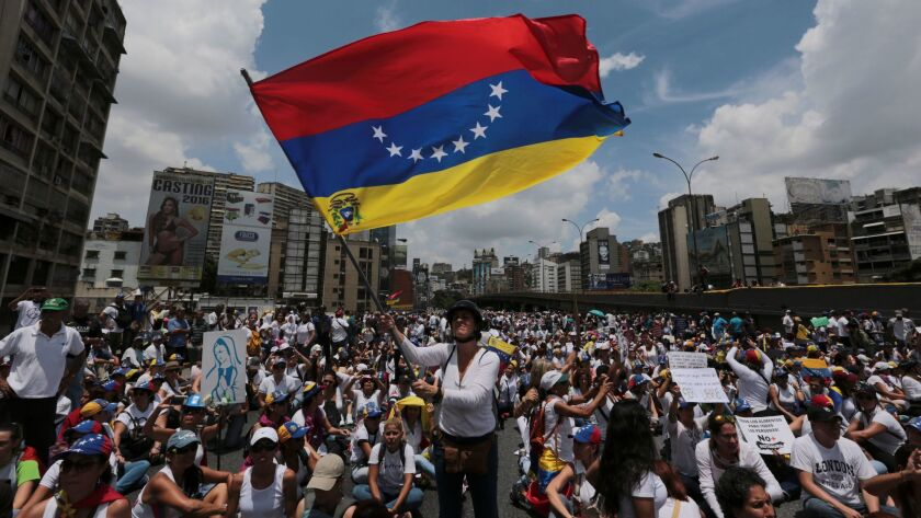 A woman waves a Venezuelan flag upside down, a distress signal, as other anti-government protesters block the Franciso Fajardo highway after their march was blocked from reaching the Interior Ministry in Caracas, Venezuela, on May 6, 2017.