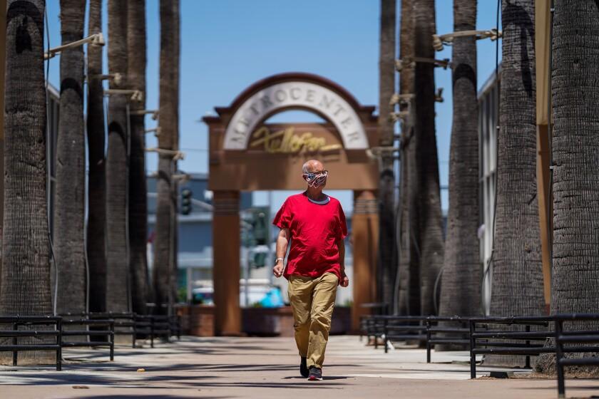 A man in a mask walks along Harbor Boulevard in downtown Fullerton last week.