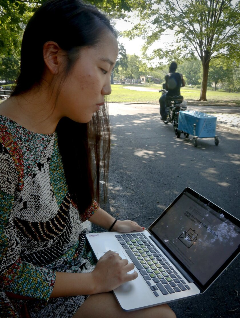 In this Thursday July 21, 2016 photo, Korean American Jaime Sunwoo shows, from her laptop, a social media collaboration letter written by a host of Asian Americans and translated for their communities to discuss and support the Black Lives Matter movement, in New York. Some Asian and Latino support