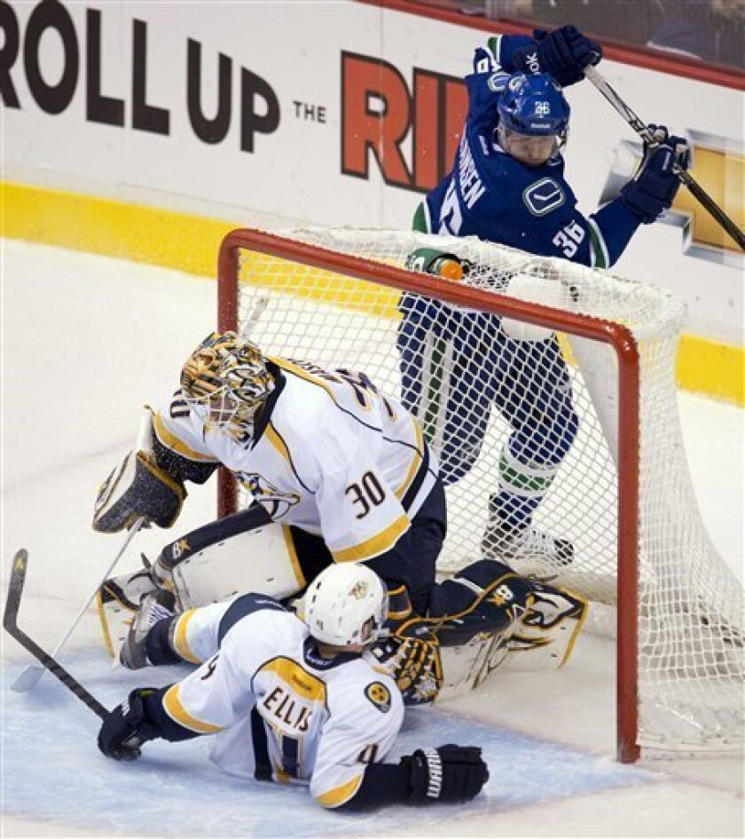 Vancouver Canucks goalie Cory Schneider (35) watches as his shot goes past Nashville Predators defenseman Ryan Ellis (4) and goalie Chris Mason (30) during the second period of their NHL hockey game, Thursday, March,14, 2013, in Vancouver. (AP Photo/The Canadian Press, Jonathan Hayward)