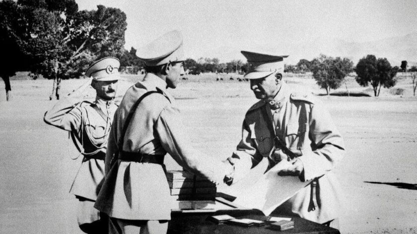 In this 1941 photo, Reza Shah Pahlavi, right, is shown handing a military commission to his second son, Ali Reza.