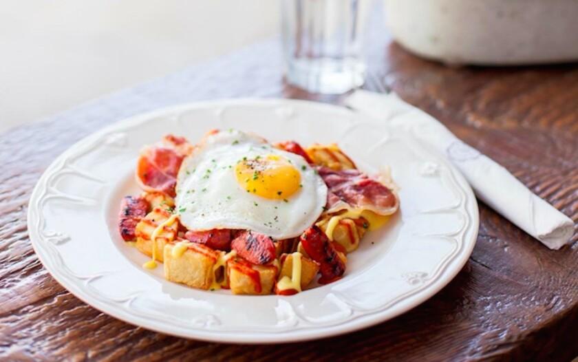 Patatas bravas comes with brava sauce, aioli, serrano ham, chorizo and an e