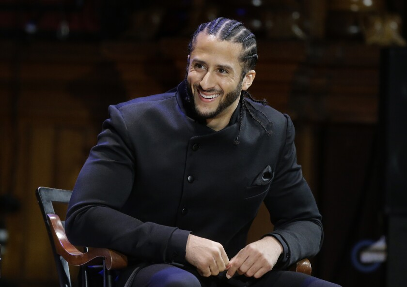"""FILE - In this Oct. 11, 2018, file photo, former NFL football quarterback Colin Kaepernick smiles on stage during W.E.B. Du Bois Medal ceremonies at Harvard University, in Cambridge, Mass. Kaepernick will release a series of books through the children's publisher Scholastic, starting with a picture story """"I Color Myself Different"""" coming out in April, (AP Photo/Steven Senne, File)"""