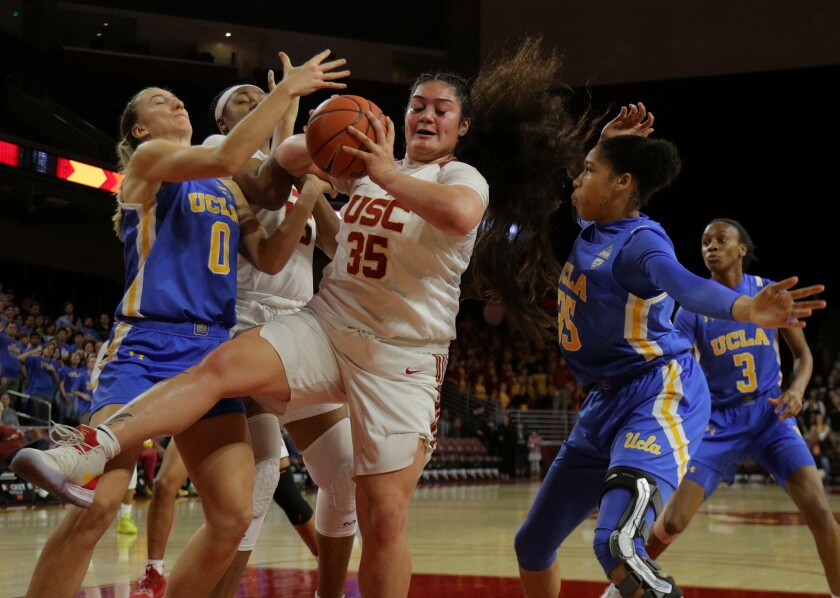 USC forward Alissa Pili boxes out UCLA's Chantel Horvat (0) and Camryn Brown (35) as she grabs a defensive rebound during a game at Galen Center on Jan. 17.