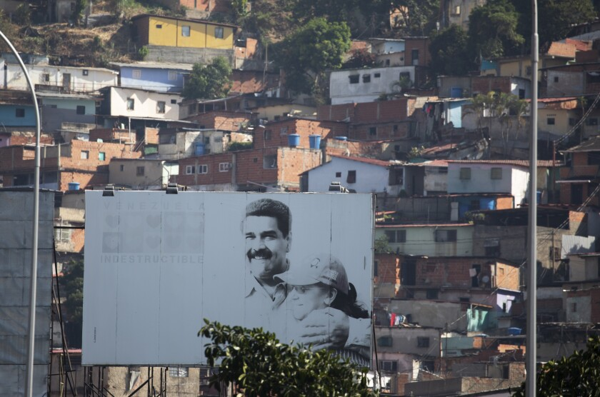 A billboard, backdropped by the Catia neighborhood, promotes an image of Venezuelan President Nicolas Maduro and first lady Cilia Flores in Caracas, Venezuela, Saturday, May 23, 2020. Bruised by years of economic calamity and more recently by U.S. sanctions, Maduro appealed for international help to deal with the new coronavirus pandemic in March even before the country's first confirmed case. (AP Photo/Ariana Cubillos)
