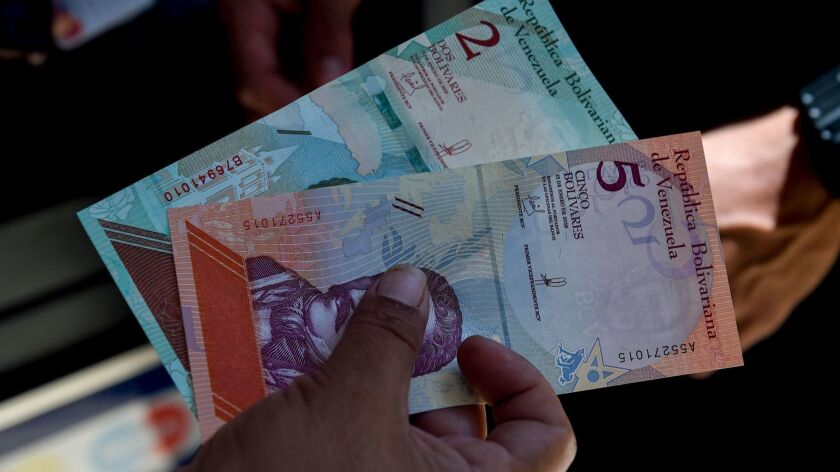 A man shows new 5-bolivar notes in Caracas on Monday.
