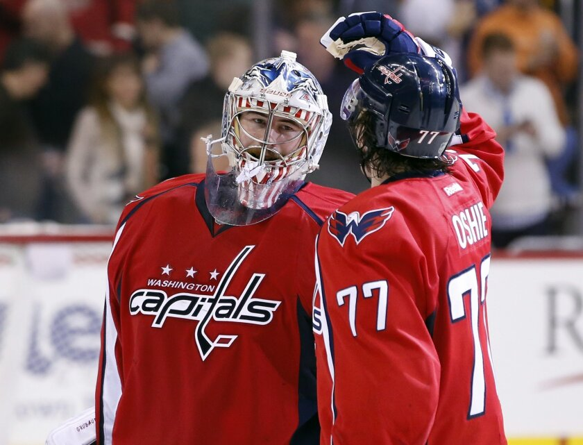 Washington Capitals goalie Philipp Grubauer (31), from Germany and right wing T.J. Oshie (77) celebrates after an NHL hockey game against the Los Angeles Kings, Tuesday, Feb. 16, 2016, in Washington. The Capitals won 3-1. (AP Photo/Alex Brandon)