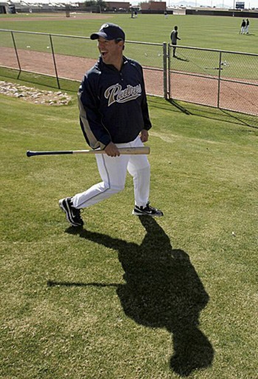 Greg Maddux laughs with a friend Wednesday as he walks to a practice field during his first day as a special instructor at the Padres' spring training camp in Peoria, Ariz.