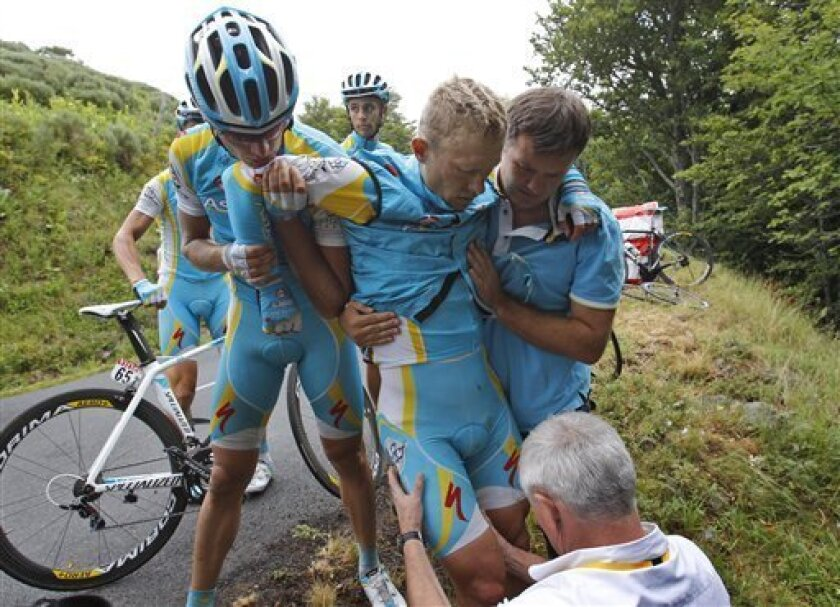 A Tour de France docotr examines the right leg of Alexande Vinokourov of Kazakhstan aftre he crashed during the 9th stage of the Tour de France cycling race over 208 kilometers (129 miles) starting in Issoire and finishing in Saint Flour, central France, Sunday July 10, 2011. (AP Photo/Christophe Ena)