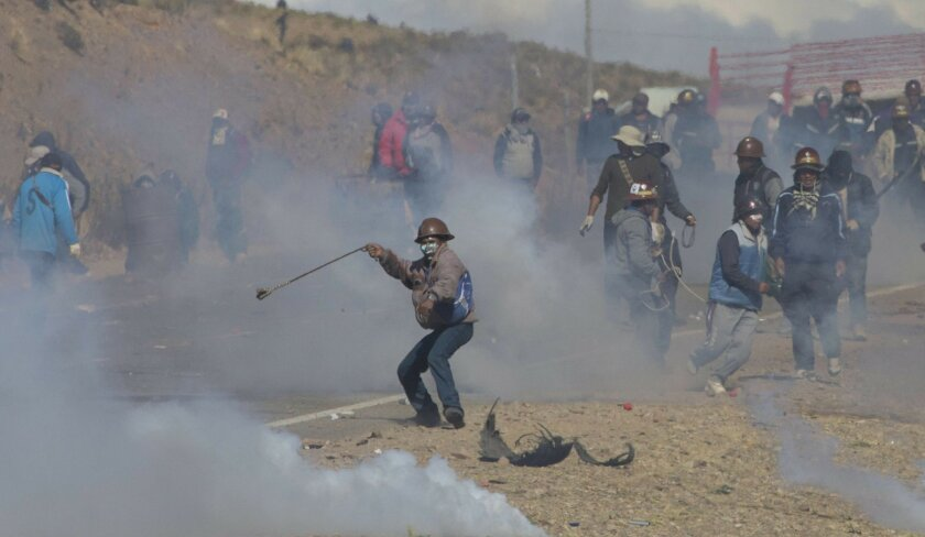 Independent miners clash with the police as they run from clouds of tear gas during  protests in Panduro, Bolivia, Thursday, Aug. 25, 2016. Thousands of independent miners continued their protests with roadblocks which precipitated the clashes as the police attempted to dislodge them. (AP Photo/Jua