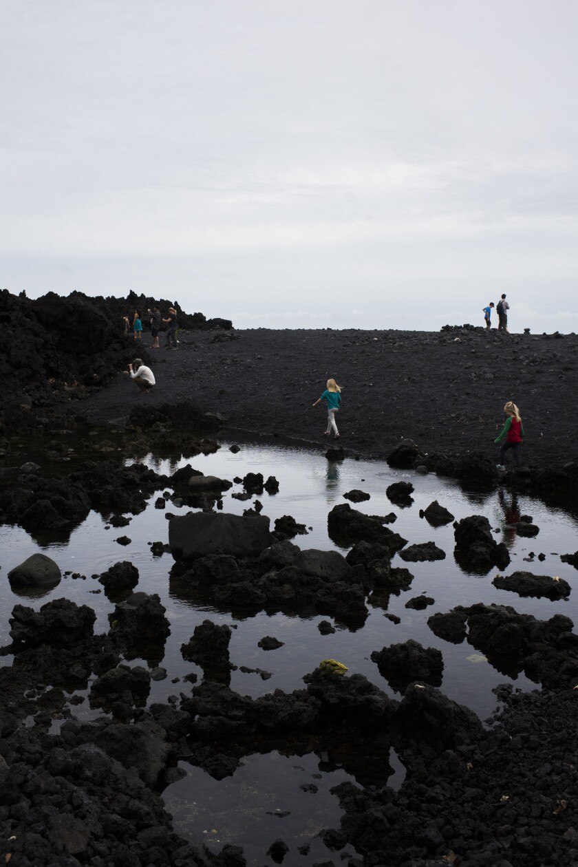 Tourists explore by a tide pool at Pohoiki's new black sand beach, created by the recent lava flow in Puna, Hawaii.