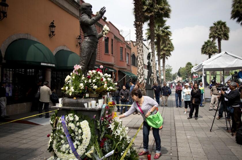 Una estatua del cantautor mexicano Juan Gabriel convertida en un monumento memorial improvisado en la Plaza Garibaldi de la Ciudad de México. Juan Gabriel, quien fue un ícono de la música latina murió el domingo en California. (AP Foto/Eduardo Verdugo)