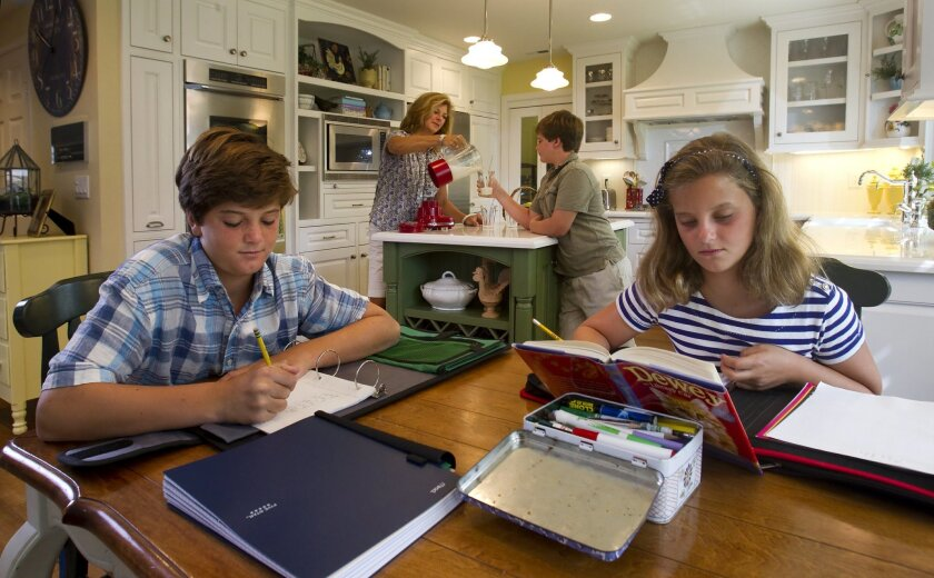 Max Rosoff, 13, (left) and his sister, Jaden, 9, do their work at the kitchen table while their mom, Julie Rosoff, pours a drink for their brother, Jack, 11. This family friendly Carmel Valley kitchen was designed by Deborah Gordon.