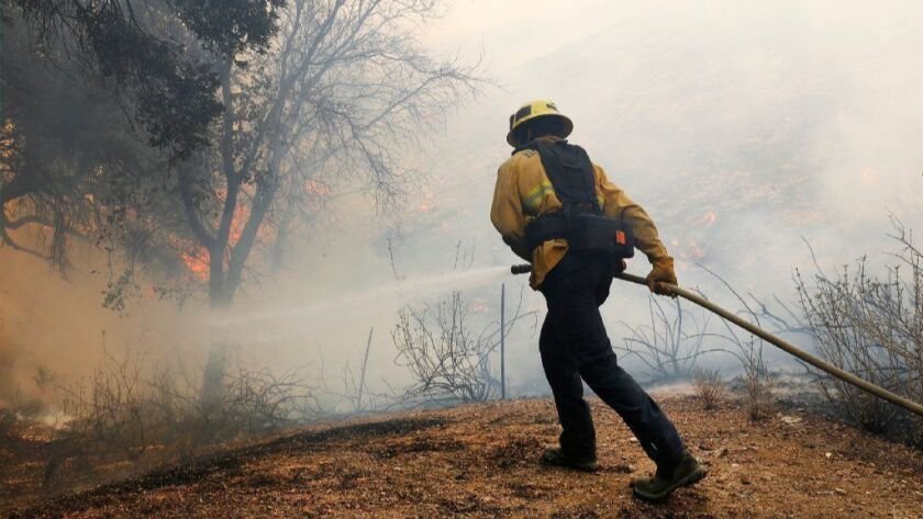 Ventura County firefighter Kyle Morrell douses flames in brush behind homes along Skelton Canyon Circle in the North Ranch area of Westlake Village on Nov. 9, 2018, as the Woolsey fire burned.