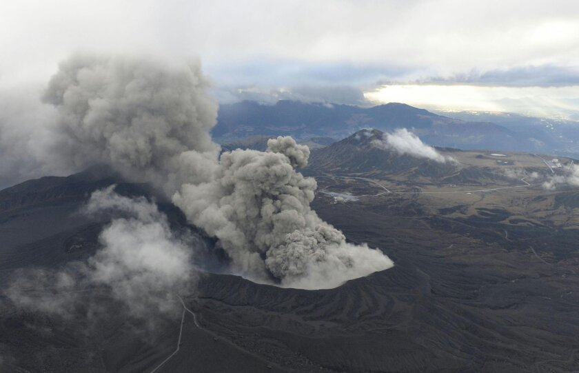 In this Nov. 26, 2014 photo, volcanic smoke billows from Mount Aso, Kumamoto prefecture, on the southern Japanese main island of Kyushu. The volcano is blasting out chunks of magma in the first such eruption in 22 years, causing flight cancellations and prompting warnings to stay away from its crat