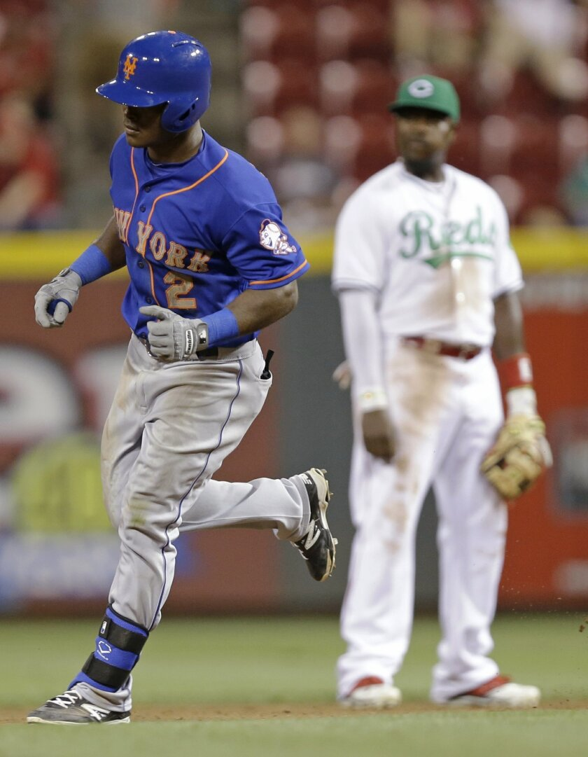 New York Mets' Dilson Herrera (2) rounds the bases past Cincinnati Reds second baseman Brandon Phillips after hitting a solo home run in the eighth inning of a baseball game, Friday, Sept. 5, 2014, in Cincinnati. (AP Photo/Al Behrman)