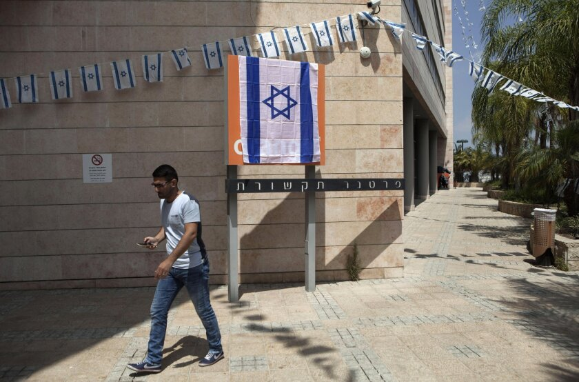 An Israeli man walks past the Orange company logo covered with an Israeli flag at Partner Communications' offices in Rosh Haayin, Israel, on June 4.
