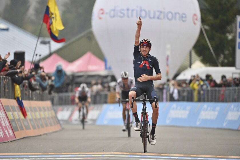 Britain's Tao Geoghegan Hart celebrates as he crosses the finish line to win the 15th stage of the Giro d'Italia cycling race, from Rivolto to Piancavallo, Italy, Sunday, Oct. 18, 2020. (Massimo Paolone/LaPresse via AP)