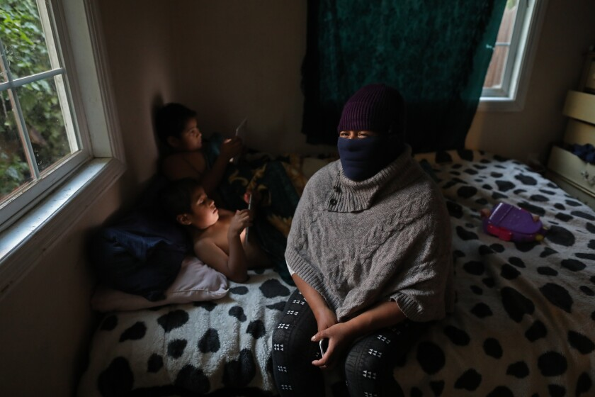 Odilia Leon wears a mask sitting on her bed with two of her children using electronic tablets