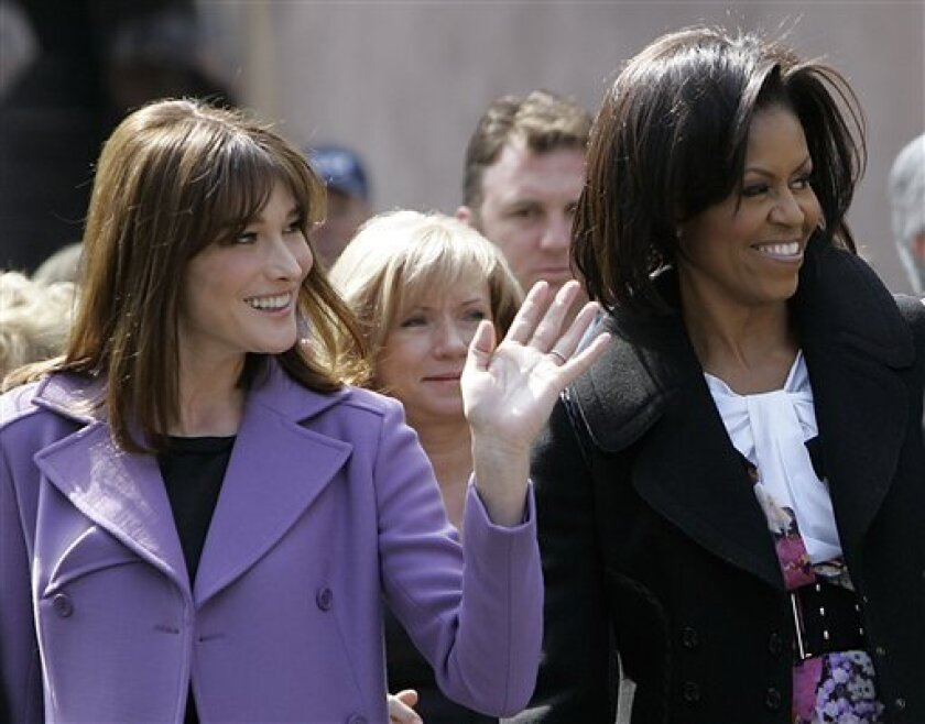 FILE - In this April 4, 2009 file photo, first lady Michelle Obama and France's then-first lady Carla Bruni-Sarkozy visit Strasbourg Cathedral in Strasbourg, France. New documents show that former French President Nicolas Sarkozy and his wife Carla Bruni showered President Barack Obama and his family with more than $41,000 worth of gifts in 2011. (AP Photo/Frank Augstein, File)