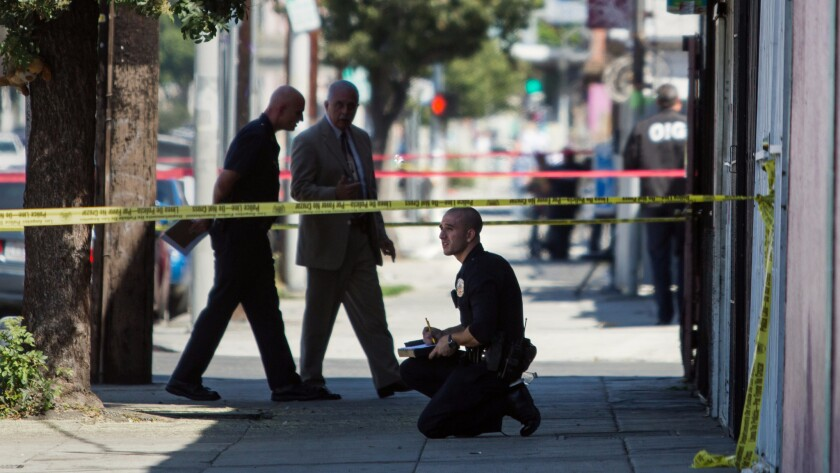 Investigators examine the scene near downtown L.A. where two Los Angeles police officers shot and killed Norma Guzman, a 37-year-old woman who police say was carrying a knife.