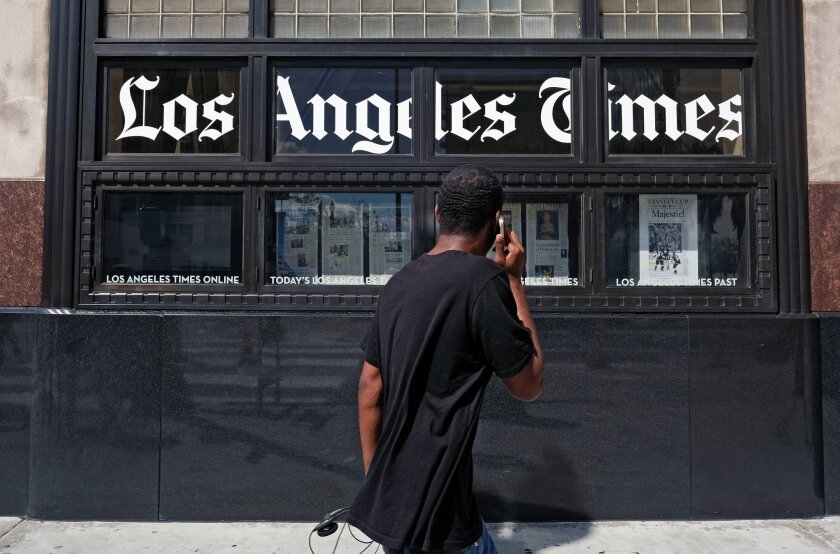 A pedestrian walks past the Los Angeles Times building in downtown Los Angeles on Monday, Oct. 5, 2015. In a memo that was obtained by The Associated Press on Monday, Tribune Publishing, the owner of the Los Angeles Times, Chicago Tribune and other newspapers, says it is offering buyouts to employe
