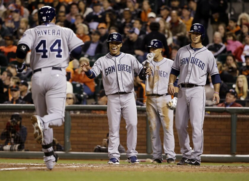 San Diego Padres' Rene Rivera (44) is greeted at the plate by teammates Alexi Amarista, center left, and Tommy Medica, right, after Rivera's three-run home run against the San Francisco Giants during the fifth inning of a baseball game Monday, April 28, 2014, in San Francisco. (AP Photo/Marcio Jose Sanchez)