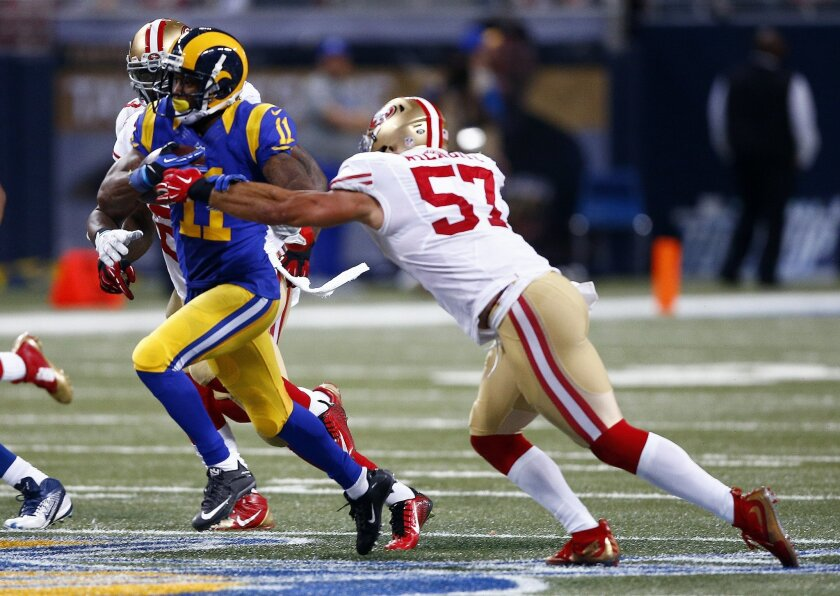 St. Louis Rams wide receiver Tavon Austin, left, runs past San Francisco 49ers inside linebacker Michael Wilhoite (57) after catching a short pass and running it for a 66-yard touchdown during the second half of an NFL football game Sunday, Nov. 1, 2015, in St. Louis. (AP Photo/Billy Hurst)
